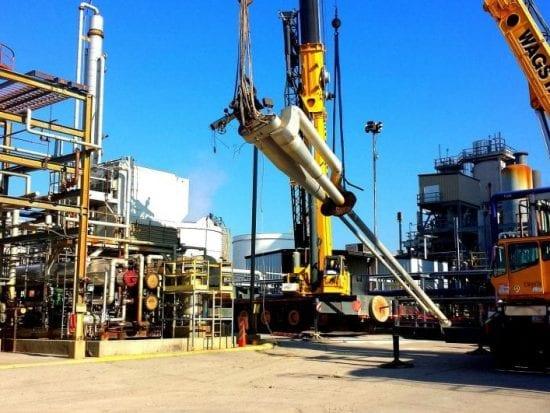 Large machine equipment lifting a large mechanical part.